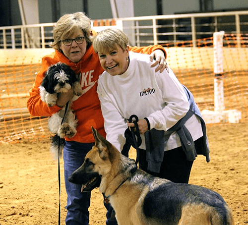 two happy dog owners at a dog training course